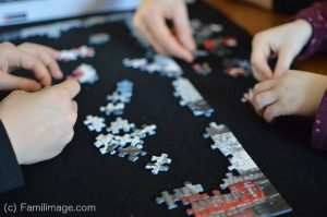 Several pairs of hands solving a jigsaw puzzle
