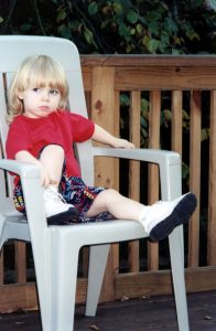Photo of a young child sitting on a chair for a time out
