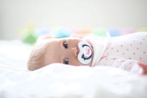 Photo d'un bébé allongé dans son lit mais réveillé