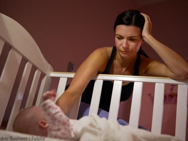 Photo d'une mère fatiguée penchée au-dessus du lit de son bébé